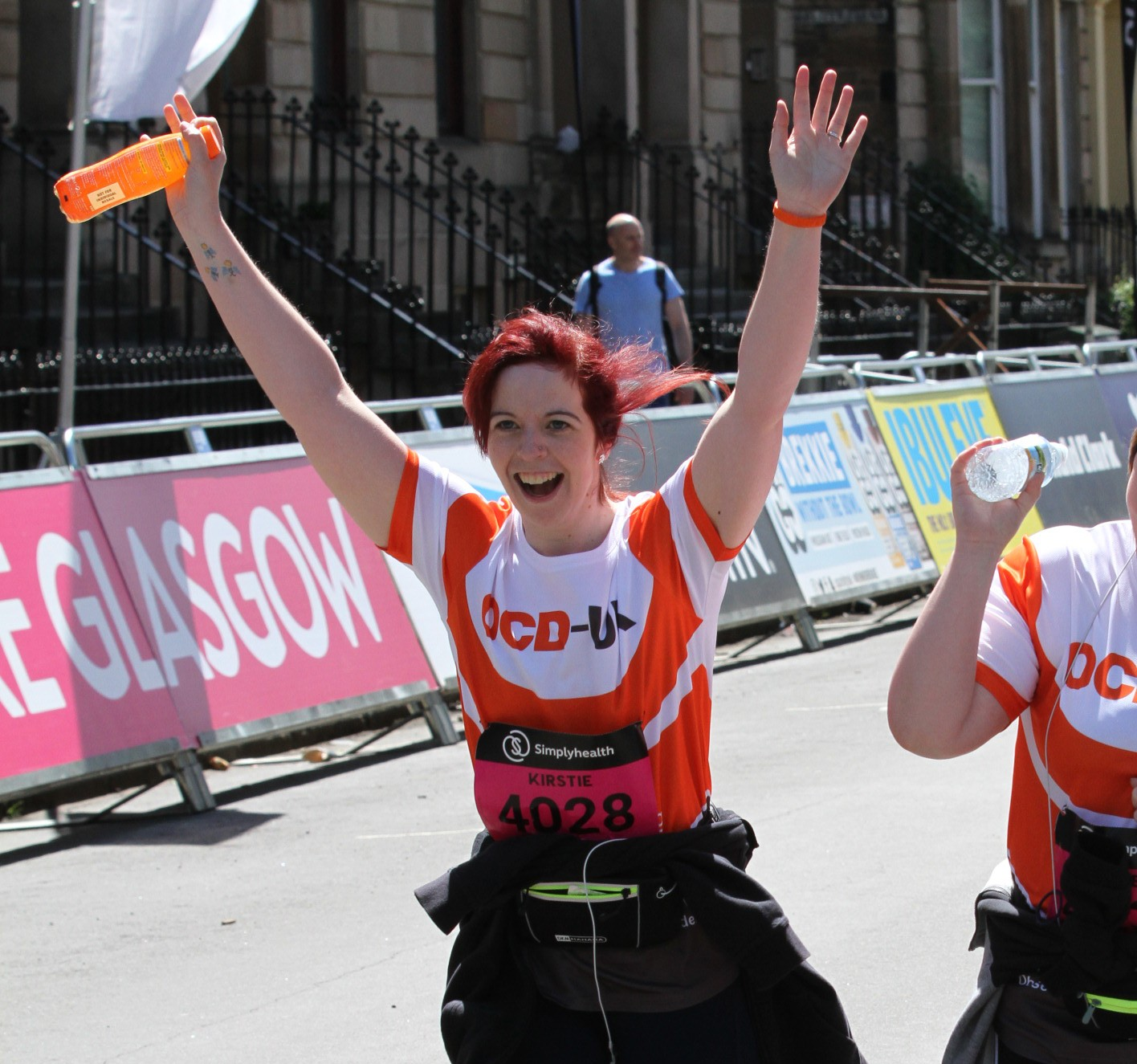 Kirstie crosses the finish line with her OCD-UK t-shirt and beaming smile with her arms in the air.