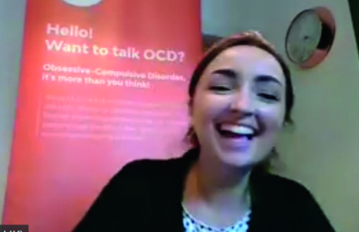 Picture of a smiling Zoe sitting in front of an orange OCD-UK banner with the words 'Hello, want to talk OCD?'